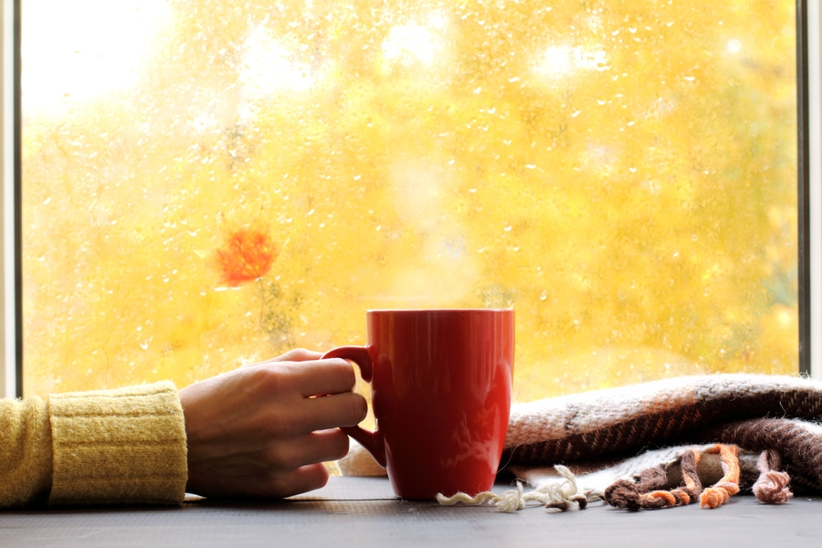 red mug of hot drink, when behind a window is rain in autumn