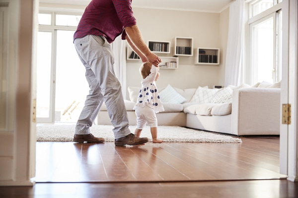 Father helping daughter learn to walk at home, side view. What Indoor Air Quality Accessories Can Help Keep Me Healthy?